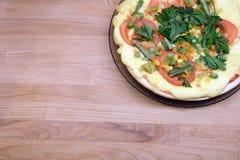 Pizza apetitosa con los tomates, el maíz y los guisantes verdes en la placa redonda en la opinión superior del fondo de madera Imagenes de archivo