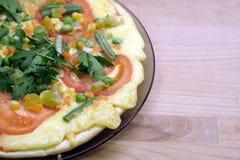 Pizza apetitosa con los tomates, el maíz y los guisantes verdes en la placa redonda en la opinión superior del fondo de madera Fotos de archivo libres de regalías