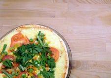 Pizza apetitosa con los tomates, el maíz y los guisantes verdes en la placa redonda en la opinión superior del fondo de madera Imagen de archivo libre de regalías