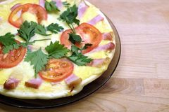 Pizza apetitosa con los tomates, el tocino y el queso en la placa redonda en la opinión superior del fondo de madera Fotografía de archivo