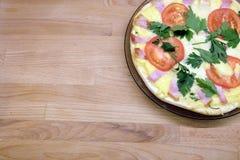 Pizza apetitosa con los tomates, el tocino y el queso en la placa redonda en la opinión superior del fondo de madera Imagenes de archivo
