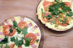 Pizza apetitosa con los tomates, la carne, el maíz y los guisantes verdes en las placas redondas en la opinión superior del fondo Foto de archivo