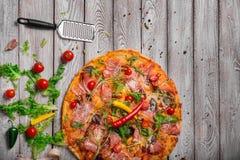 Pizza appena fatta con una scapola su una tavola Pizza su un fondo rustico Pizza con formaggio arrostito e pepe piccante fotografie stock