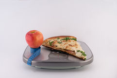 Pizza and Apple on Scales. Pizza, tape measure and apple on scales on white background royalty free stock photo