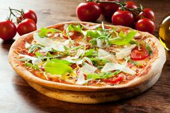 Pizza Arugula. Freshly prepared pizza with arugula, tomatoes and parmesan cheese royalty free stock images
