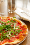 Pizza with arugula on table Stock Images