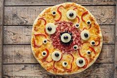 Pizza assustador do monstro do alimento de Dia das Bruxas com os olhos na tabela de madeira do vintage Imagens de Stock Royalty Free