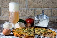 Pizza auf dem Tisch mit einem Glas Bier und Bestandteilen Lizenzfreies Stockfoto