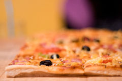 Pizza auf einem Hintergrund des hölzernen Brettes Stockbild