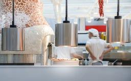 Pizza auf erhitzter Platte mit Ofen herein und unidentifizierbaren Chefs im Hintergrund stockfotografie