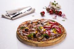 Pizza auf hölzerner Platte Stockbilder