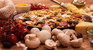 Pizza avec des ingrédients sur une table - plan rapproché Photographie stock