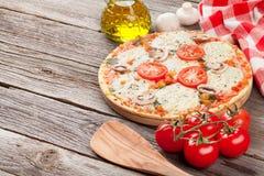 Pizza avec des tomates et des champignons de couche image libre de droits