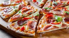 Pizza avec du fromage de mozzarella, la sauce de jambon et tomate, le salami, le poivre, les épices et l'arugula frais Pizza ital photo stock