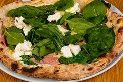 Pizza avec du jambon et des épinards images libres de droits