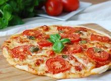 Pizza avec du jambon, les tomates, le mozzarella et le basilic Photos stock