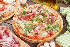 Pizza avec le prosciutto, les tomates et les champignons photos stock