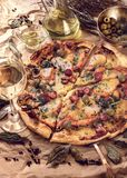 Pizza avec les saucisses, le jambon et les olives Près de l'huile d'olive et du vin blanc images libres de droits