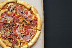 Pizza avec les tomates, le lard, le salami, le fromage et les champignons dans une boîte en carton sur le fond foncé, vue supérie Photos libres de droits