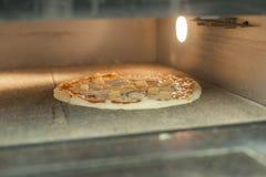 Pizza-Backen im Ofen Stockbilder