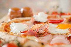 Pizza with bacon, eggs, sour creme and pepperoni - Shallow dept of field. Pizza with bacon, eggs, sour creme and pepperoni - Blurred salt and pepper shaker and stock photography