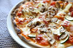 Pizza with bacon and mushroom, Italian food. Pizza with bacon and mushroom on a plate, Italian food stock photography