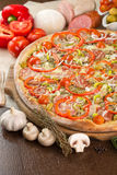 Pizza with bacon and mushrooms. Garnished with garlic, pepper, ham, olives and tomatoes Stock Photos