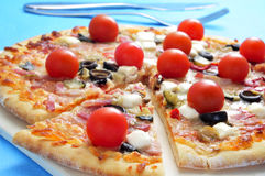 Pizza with bacon, olives, cherry tomatoes, goat cheese, green pe Stock Photography
