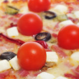 Pizza with bacon, olives, cherry tomatoes, goat cheese, green pe Stock Photos