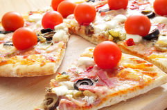 Pizza with bacon, olives, cherry tomatoes. Some slices of pizza with bacon, olives, cherry tomatoes, goat cheese, green pepper and eggplant Stock Photography