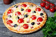 Pizza with bacon, olives and tomato Royalty Free Stock Photography