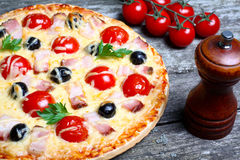 Pizza with bacon, olives and tomato Royalty Free Stock Photos