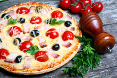 Pizza with bacon, olives and tomato Stock Photos