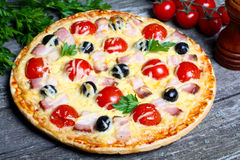 Pizza with bacon, olives and tomato Stock Image