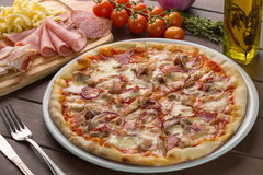 Pizza with bacon on the plate. Pizza with bacon garnished with mushrooms, pepper, ham and oil Royalty Free Stock Images