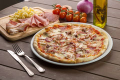 Pizza with bacon on the plate. Pizza with bacon garnished with mushrooms, pepper, ham, olives and tomatoes Royalty Free Stock Images