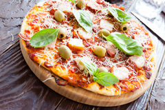 Pizza with bacon slices and olives on the board Stock Photo