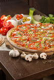 Pizza with bacon and tomatoes. Pizza with bacon garnished with mushrooms, pepper, ham, olives and tomatoes Stock Image