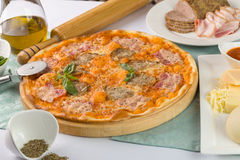 Pizza with bacon and tomatoes on the wooden plate. Pizza with bacon and tomatoes served with ingredients Royalty Free Stock Photo