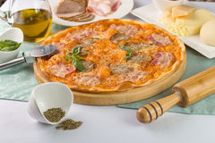 Pizza with bacon and tomatoes on the wooden plate. Pizza with bacon and tomatoes served with ingredients Royalty Free Stock Image