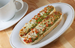 Pizza Baguettes with Tea Cup. Two scrumptious pizza baguettes with a large tea cup stock photo