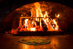 Pizza baked in a brick oven with woodfire. Pizza is a flatbread generally topped with tomato sauce and cheese and baked in an oven. It is commonly topped with a Royalty Free Stock Photos