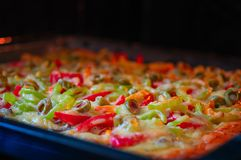 Pizza is baked in the oven. Pizza with meat, tomatoes, sweet pepper, cheese and olives. Top side view. stock images