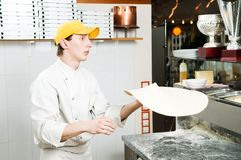 Pizza baker juggling with dough. One chef baker in white uniform juggling with bakery pastry for pizza at kitchen Royalty Free Stock Photos