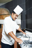 Pizza baker juggling with dough. One chef baker in white uniform juggling with bakery pastry for pizza at kitchen Royalty Free Stock Images