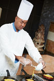 Pizza baker juggling with dough. Arab chef baker in white uniform frying omelette or pancake at kitchen Stock Photography