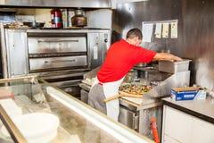 Pizza baker making fresh pizza Royalty Free Stock Image