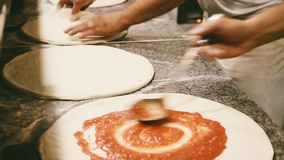 Pizza baker prepares italian pizza with tomato topping Royalty Free Stock Images