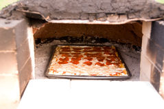 Pizza baking in earthen oven Royalty Free Stock Photography