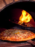 Pizza baking in the oven Stock Photography